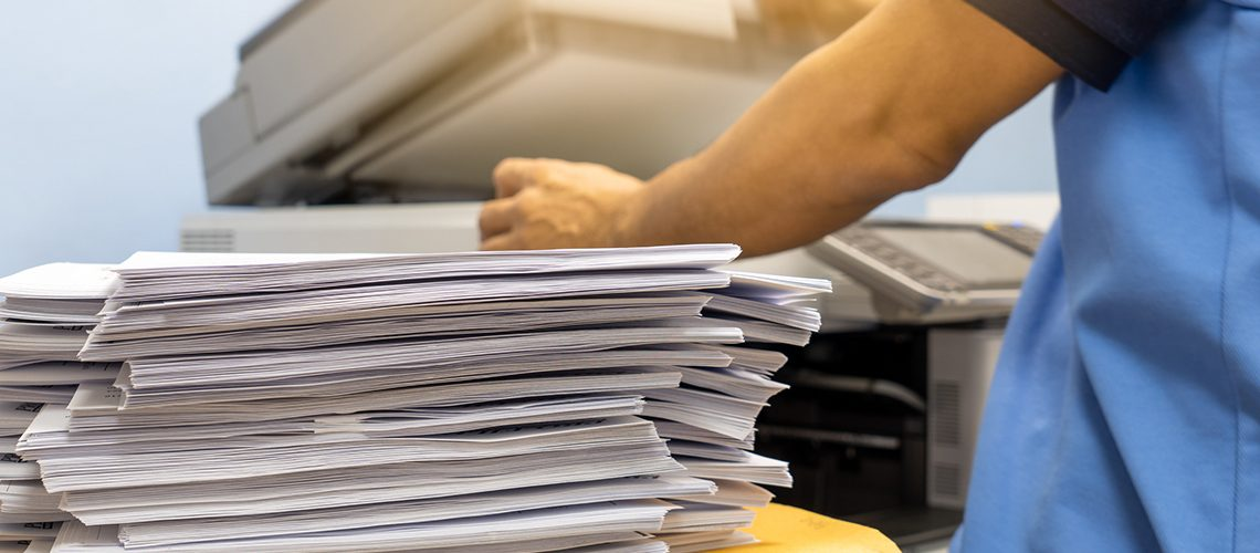 The papers stacked waiting to be copied with a copier machine.
